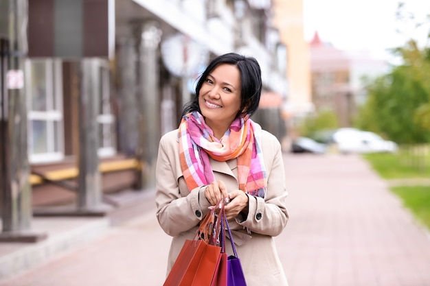 Linda mulher madura com sacolas de compras ao ar livre