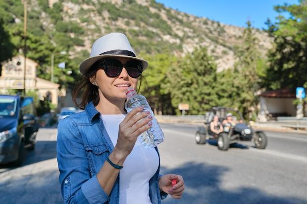 Linda mulher madura em pé na estrada da montanha bebendo água