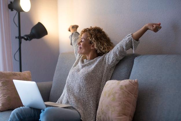 Linda mulher madura feliz no cabelo encaracolado com os braços estendidos e olhos fechados, sentado com o laptop no sofá em casa. mulher satisfeita e de bom humor sentada no sofá com o laptop e esticando os braços