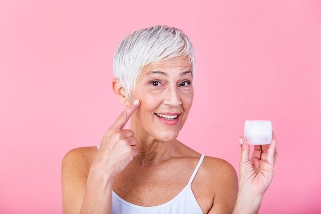 Linda mulher madura segurando o frasco de creme hidratante e olhando para a câmera. mulher sênior feliz segurando uma garrafa de loção antienvelhecimento isolada sobre fundo rosa. tratamento antienvelhecimento e beleza.