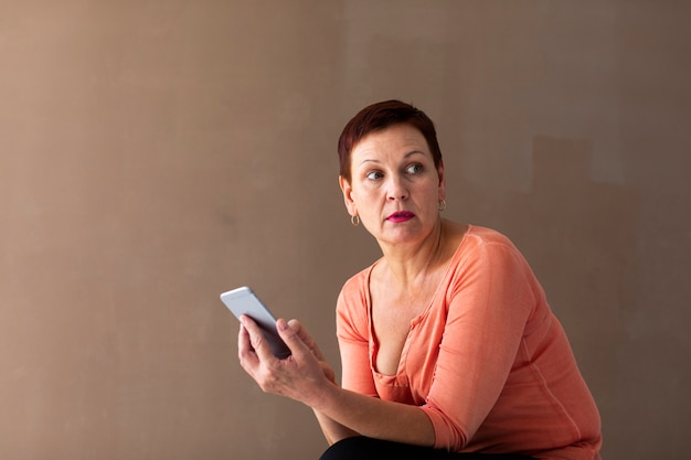 Linda mulher madura, segurando o telefone