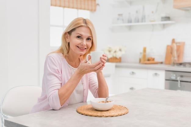 Linda mulher madura tomando café da manhã