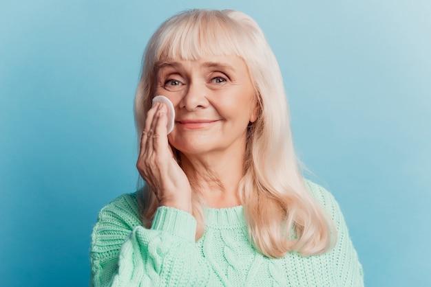 Linda mulher madura usa almofada de algodão isolada em fundo azul