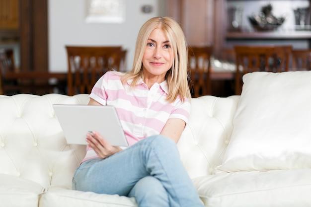 Linda mulher madura usando tablet eletrônico em casa