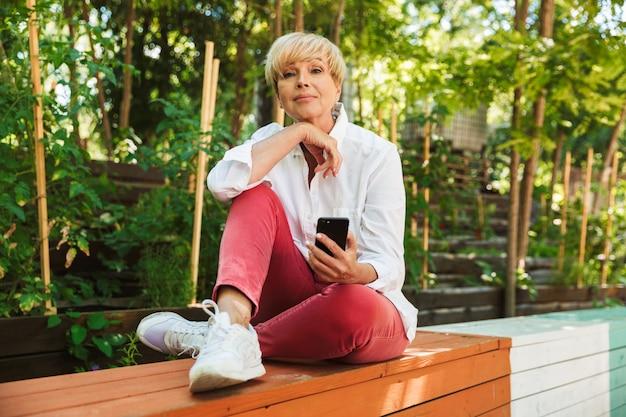 Linda mulher madura usando telefone celular