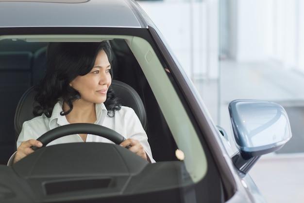 Linda mulher madura, verificando carros novos na concessionária