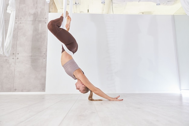 Linda mulher magra caucasiana está fazendo treinamento de alongamento em um estúdio moderno leve