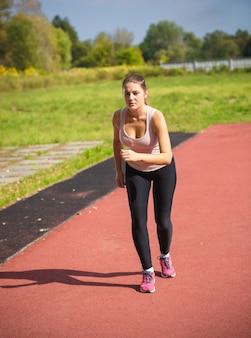Linda mulher magra correndo em um dia quente na arena esportiva