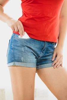 Linda mulher magra tirando camisinha de shorts jeans
