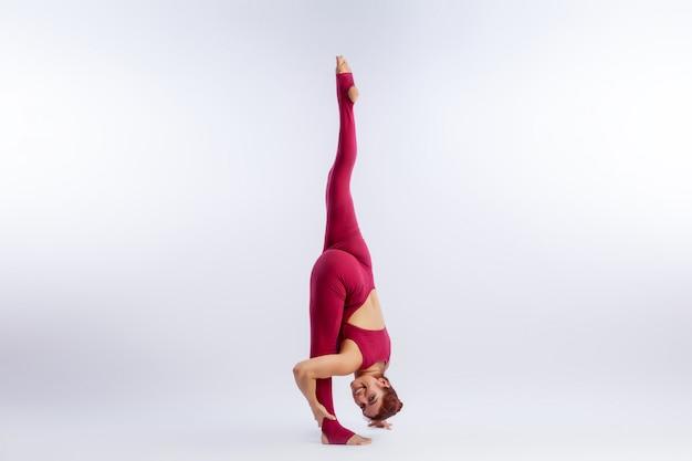 Linda mulher magro de macacão de esportes fazendo yoga
