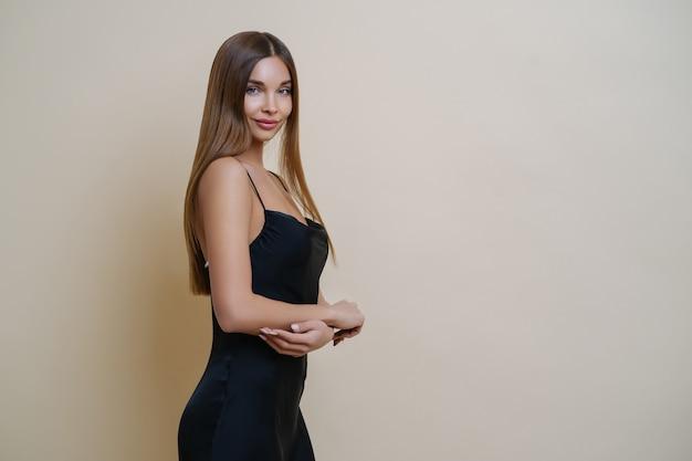 Linda mulher magro fica de perfil, usa vestido preto elegante, tem cabelo longo e reto