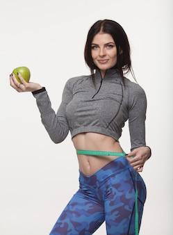Linda mulher magro, segurando a maçã verde e com várias fitas de medição de cor na cintura