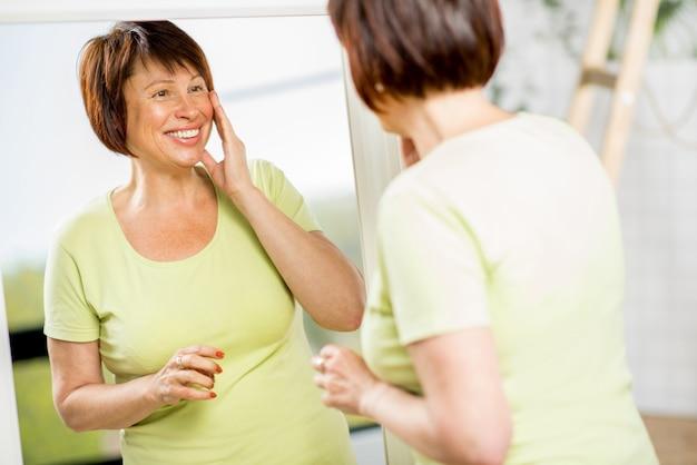 Linda mulher mais velha olhando para o rosto com um sorriso no espelho