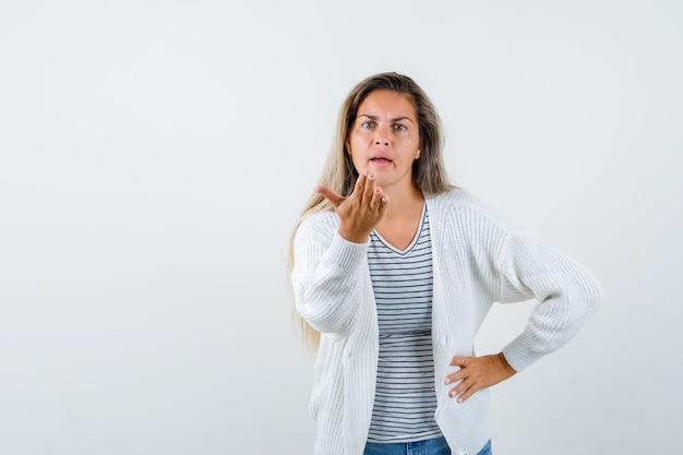 Linda mulher mantendo a mão de maneira questionadora na jaqueta e olhando ansiosa, vista frontal.