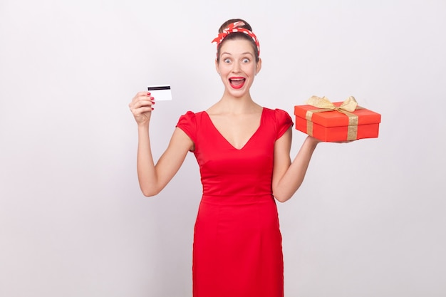 Linda mulher maravilha chocada, segurando um cartão de crédito, uma caixa de presente. interior, foto de estúdio, isolado em fundo cinza