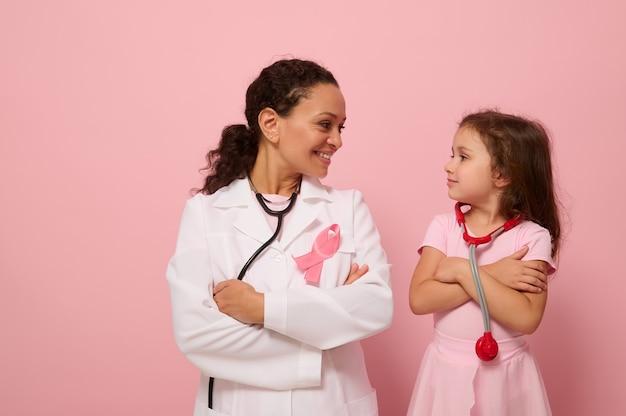 Linda mulher médica e linda menina olhando um para o outro, usando fita rosa, símbolo do dia da conscientização do câncer de mama, em pé com os braços cruzados no peito em um fundo colorido com espaço de cópia
