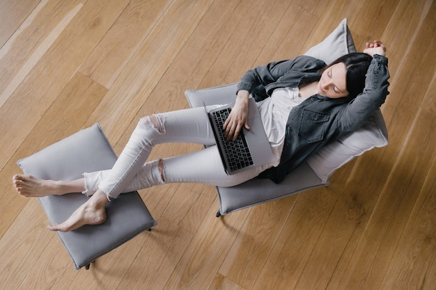 Linda mulher milenar caucasiana falando ao telefone e trabalhando em seu laptop no escritório em casa