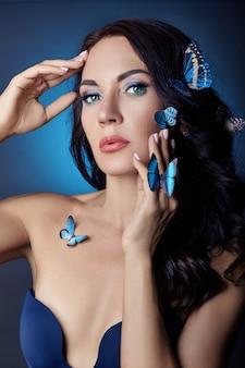 Linda mulher misteriosa com borboletas de cor azul no rosto, morena e borboletas azuis artificiais de papel no corpo das meninas. olhos verdes brilhantes, cabelo preto comprido e encaracolado