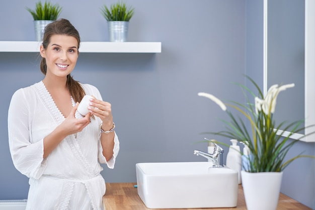 Linda mulher morena aplicando creme facial no banheiro