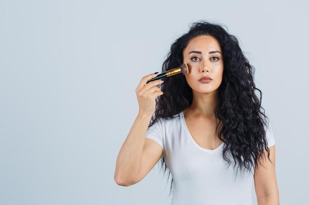 Linda mulher morena aplicando maquiagem
