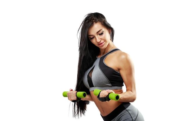 Linda mulher morena atlética bombeando os músculos com halteres. retrato isolado de uma garota fitness malhando em um fundo branco