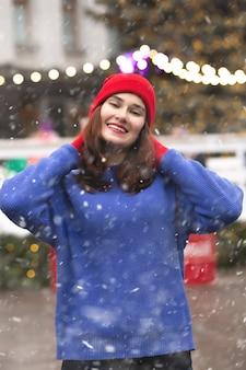 Linda mulher morena caminhando na feira de natal durante a queda de neve
