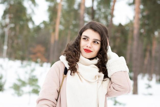 Linda mulher morena com cabelo comprido usa casaco no inverno