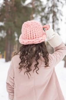 Linda mulher morena com cabelo encaracolado, usando chapéu de malha e casaco rosa olhando para a floresta no inverno