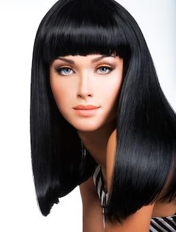 Linda mulher morena com cabelo preto comprido e liso, posando no estúdio
