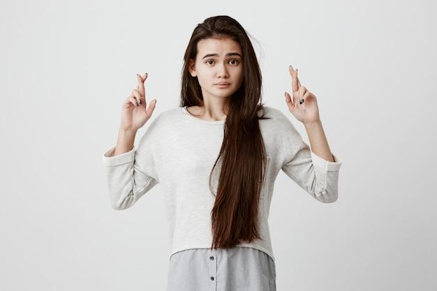 Linda mulher morena com cabelos longos, tendo um olhar excitado, supersticioso e ingênuo, mantendo os dedos cruzados, esperando boa sorte antes de passar no exame. linguagem corporal e gestos.