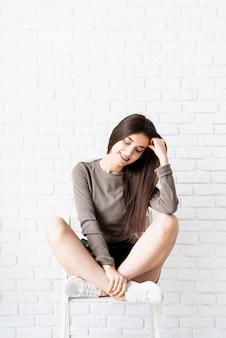 Linda mulher morena com cabelos longos, vestindo uma camisa marrom e shorts de couro preto, sentada na cadeira, pensando e sorrindo