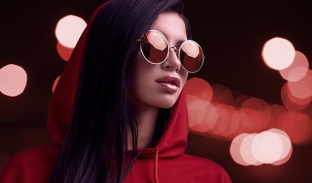 Linda mulher morena com capuz vermelho e óculos no fundo da cidade à noite