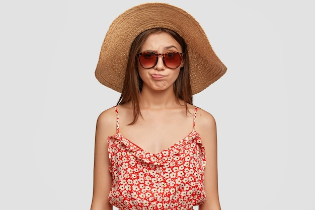 Linda mulher morena com chapéu de verão, vestido, franze os lábios em descontentamento, sente desprazer