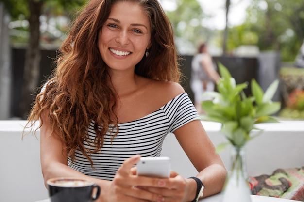 Linda mulher morena com expressão alegre e telefone no terraço ao ar livre do café