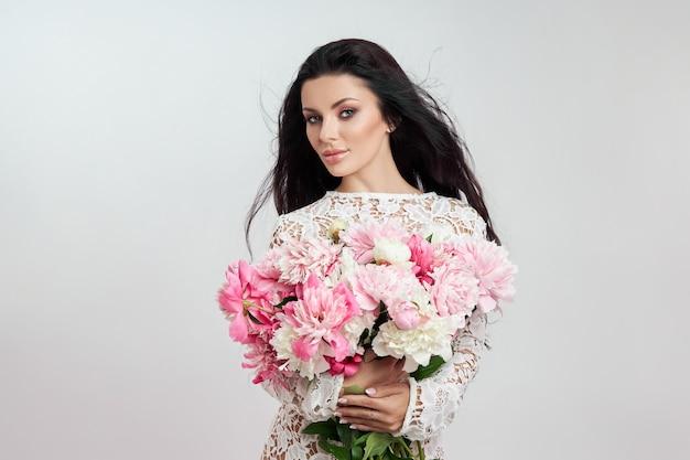 Linda mulher morena com flores peônia