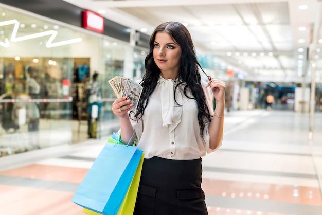 Linda mulher morena com leque de dólar no shopping