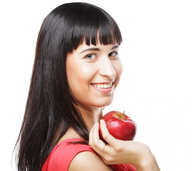 Linda mulher morena com maçã vermelha nas mãos