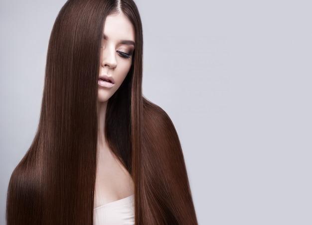 Linda mulher morena com um cabelo perfeitamente liso e maquiagem clássica