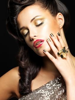 Linda mulher morena com unhas douradas e estilo de maquiagem nos olhos