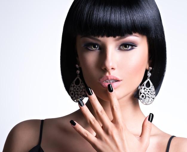 Linda mulher morena com unhas pretas e maquiagem fashion