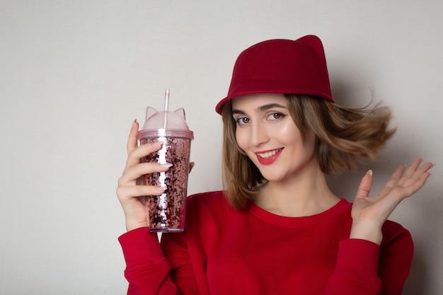 Linda mulher morena de suéter vermelho e boné segurando o copo de suco de cereja. espaço para texto