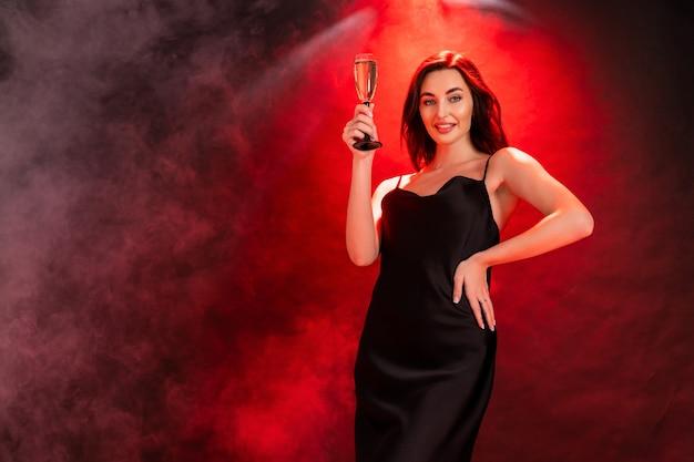 Linda mulher morena de vestido preto levanta a taça de champanhe na hora da festa conceito de férias