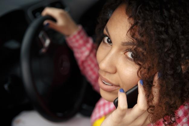 Linda mulher morena dirigindo um carro azul, falando enquanto dirige. olhando para fora, sorrindo e falando ao telefone. comprando carro novo.