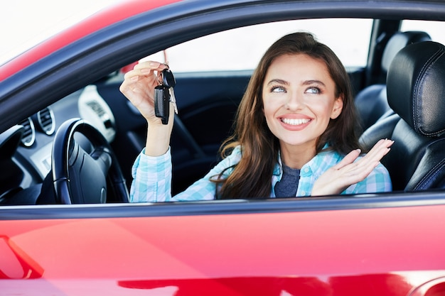 Linda mulher morena dirigindo um carro vermelho, comprando um automóvel. feliz proprietário de carro novo, olhando para o lado, segurando as chaves do carro e sorrindo. cabeça e ombros, motorista feliz