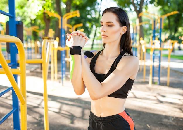 Linda mulher morena e musculosa, flexível, vestindo roupa esportiva preta