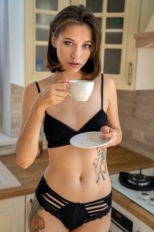 Linda mulher morena em lingerie em casa na cozinha com uma xícara de café