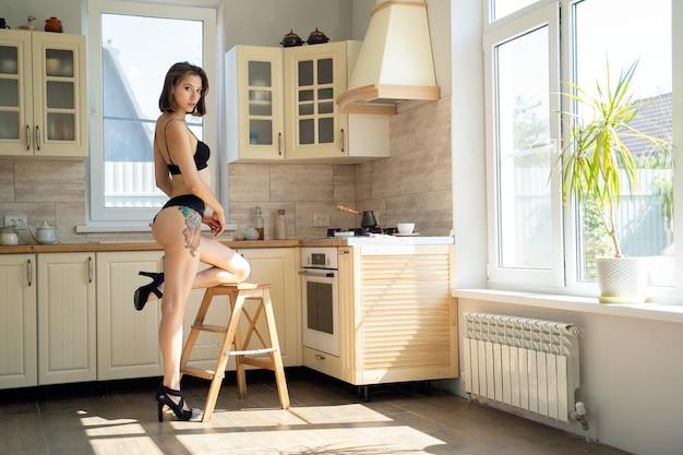 Linda mulher morena em lingerie em casa na cozinha