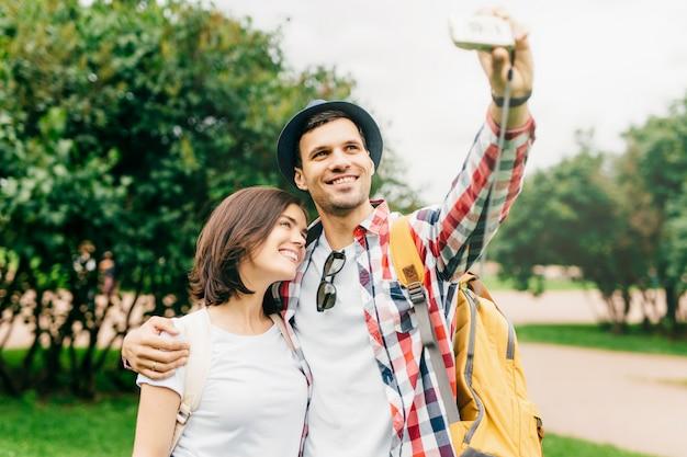 Linda mulher morena em pé perto de seu marido, posando na câmera enquanto faz selfie, tendo alegria juntos enquanto passa suas férias na cidade grande, explorando novos locais de interesse
