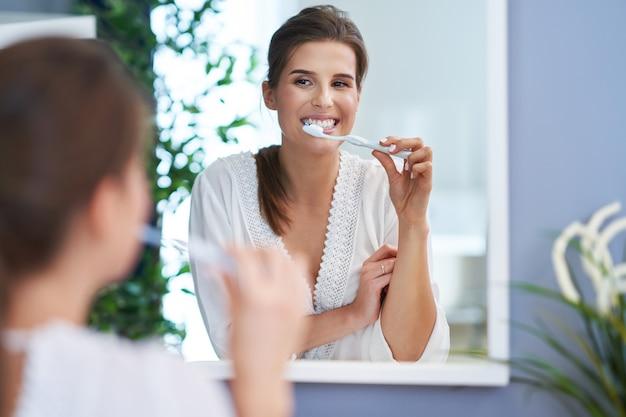 Linda mulher morena escovando os dentes no banheiro