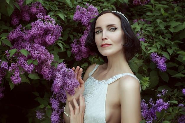 Linda mulher morena está entre os arbustos que florescem lilás no jardim.